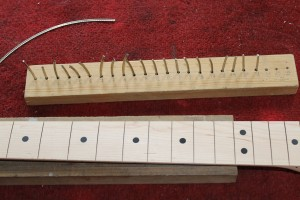 The fret wire is cut to length and kept in order of size in a wooden block
