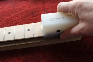 A Stewart Macdonald fret beveling file is used to dress the fret ends