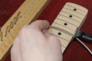 The fret wire is cut to length using pincers