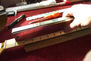 Using a sanding bar to level the frets